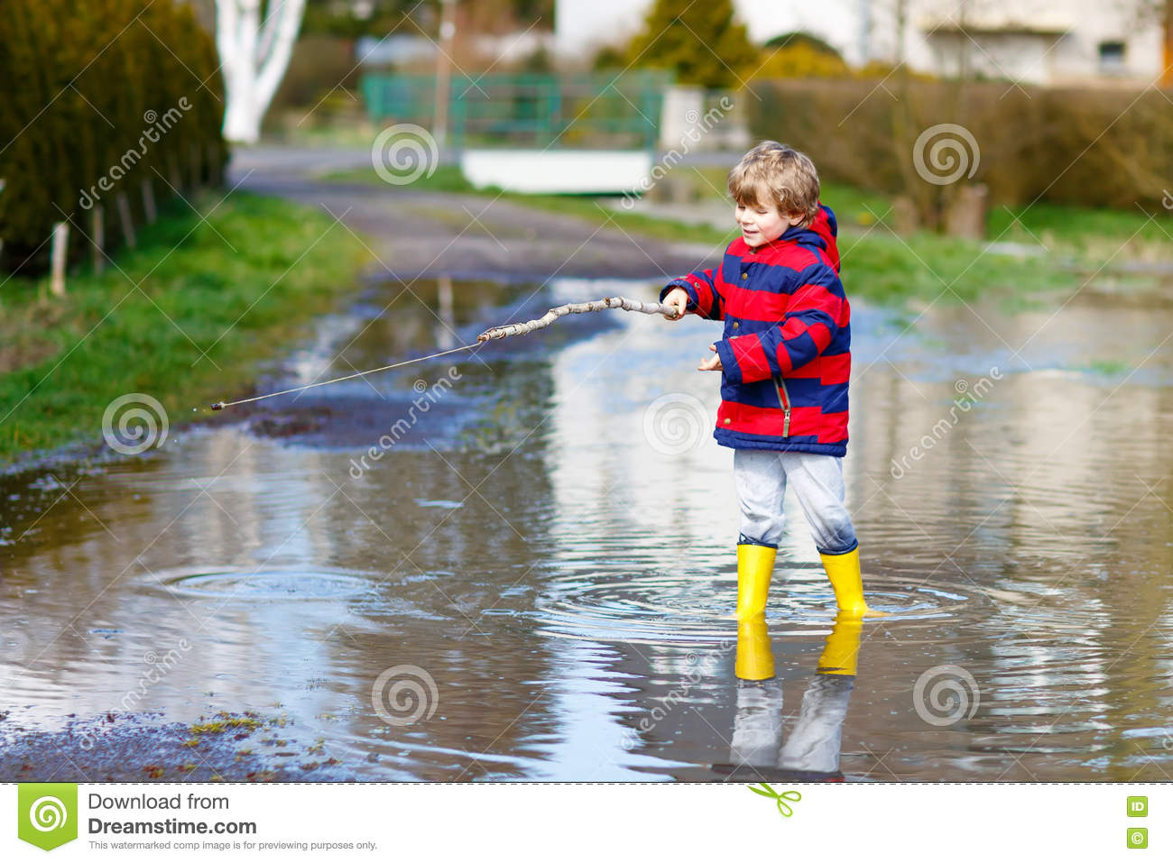 Little kid boy playing with fishing rod by puddle stock for Little kid fishing pole