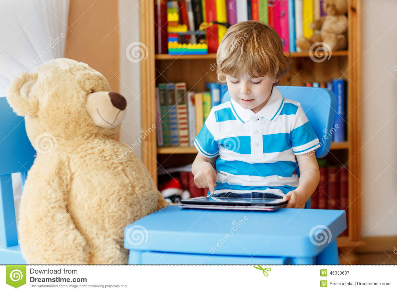 Little Kid Boy Playing With Tablet Computer In His Room At