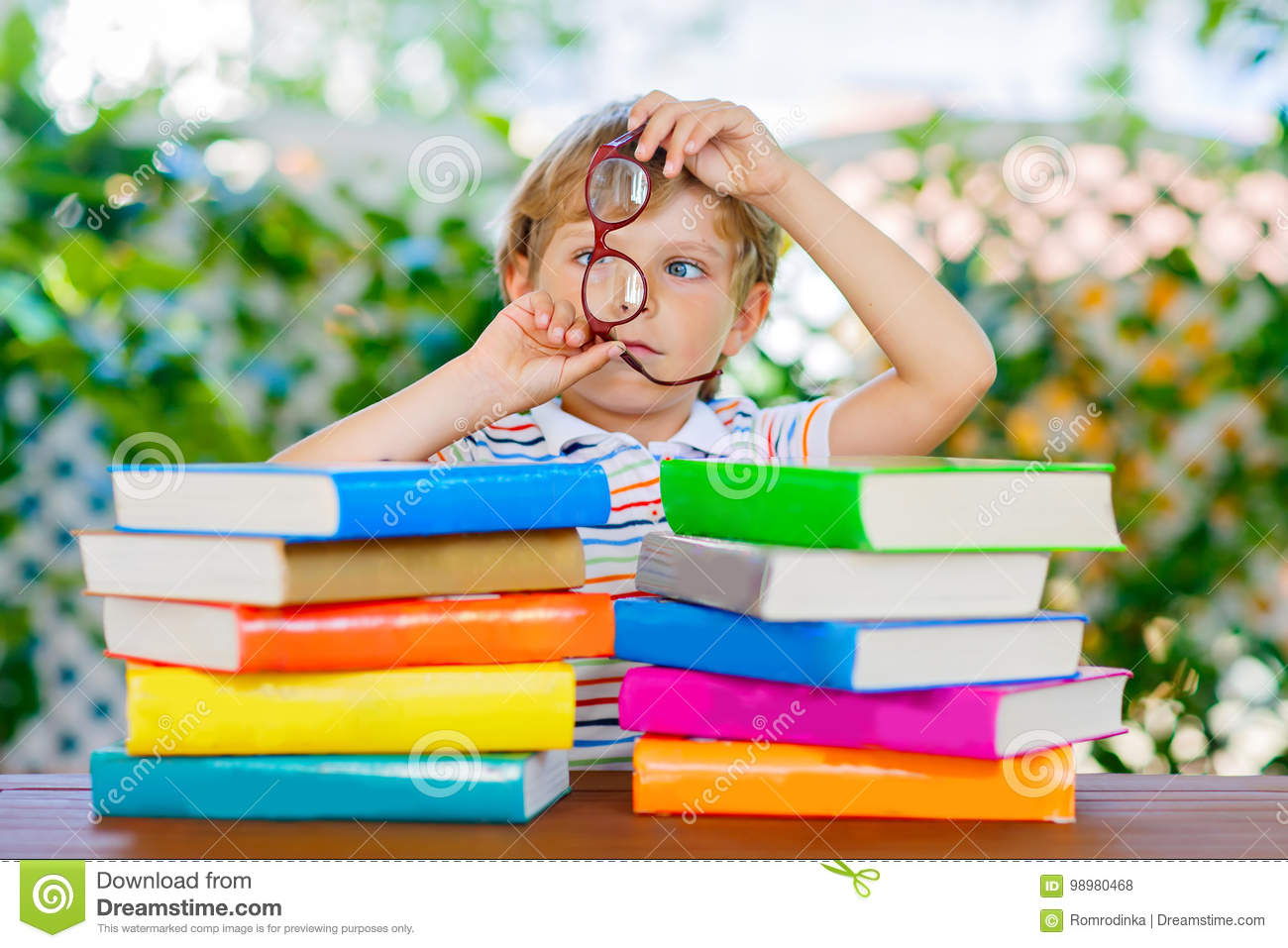 5fdf2d470a Beautiful little kid boy with glasses and stack of colorful books. Cute  happy preschool child and student is back to school and reading on warm day.
