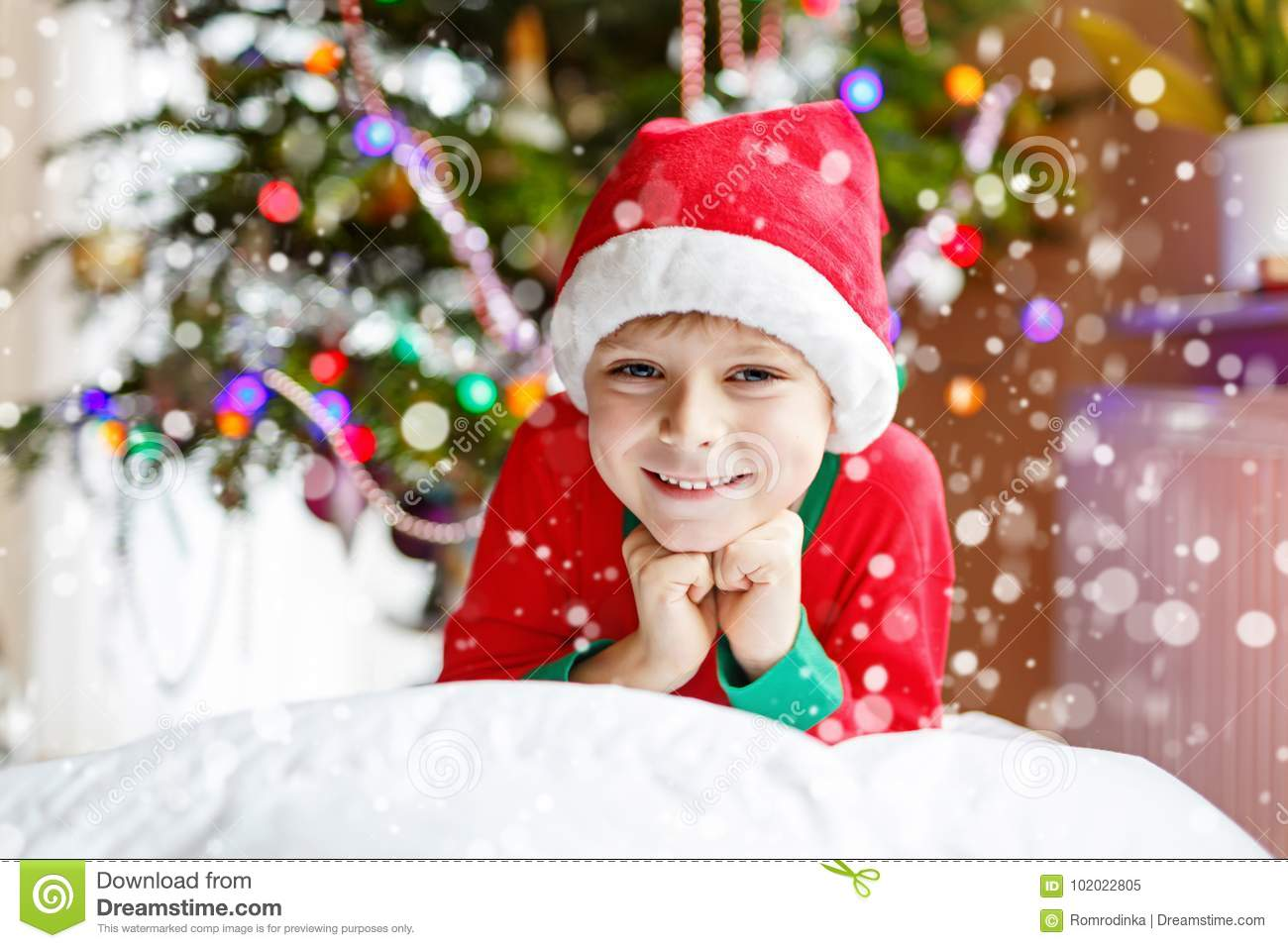 d102283c45c Little kid boy in santa hat with Christmas tree and lights on background.