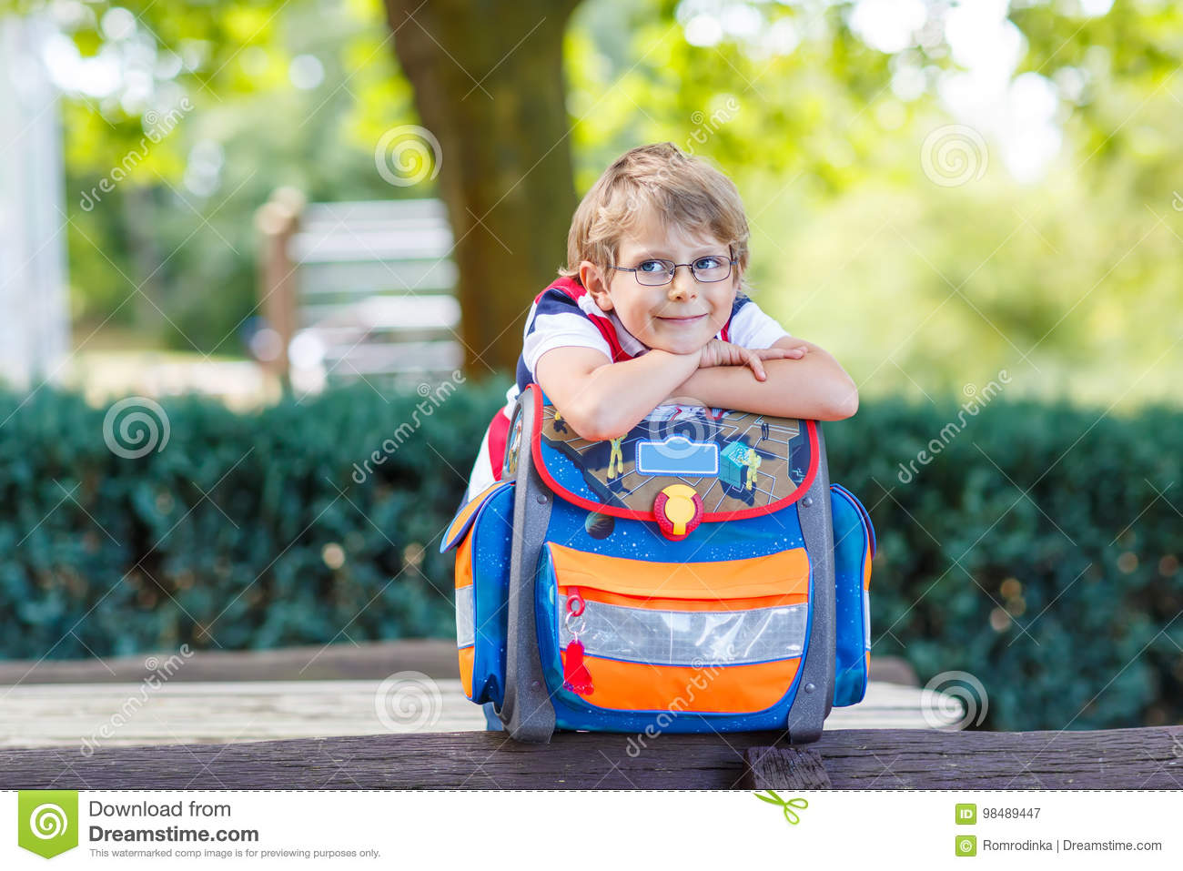 Little kid boy with school satchel on first day to school