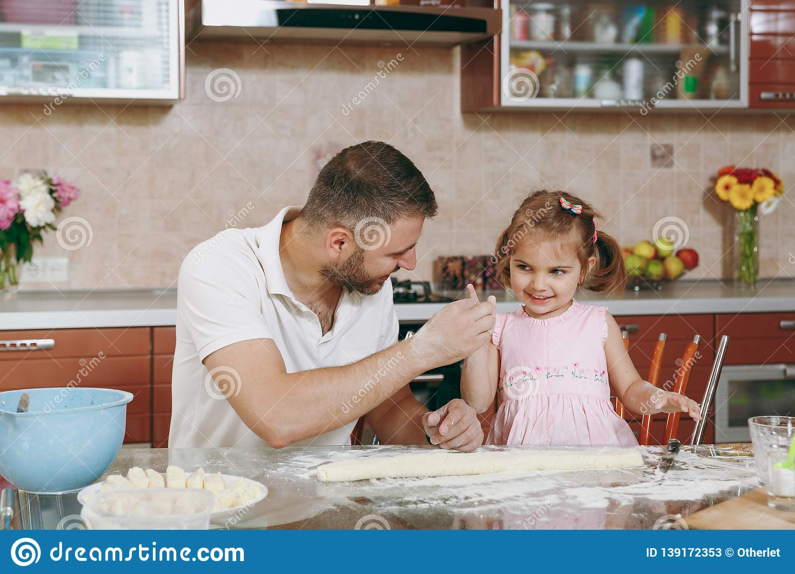 Little kid girl helps man to cook lazy dumplings, play in light kitchen at table. Happy family dad, child daughter