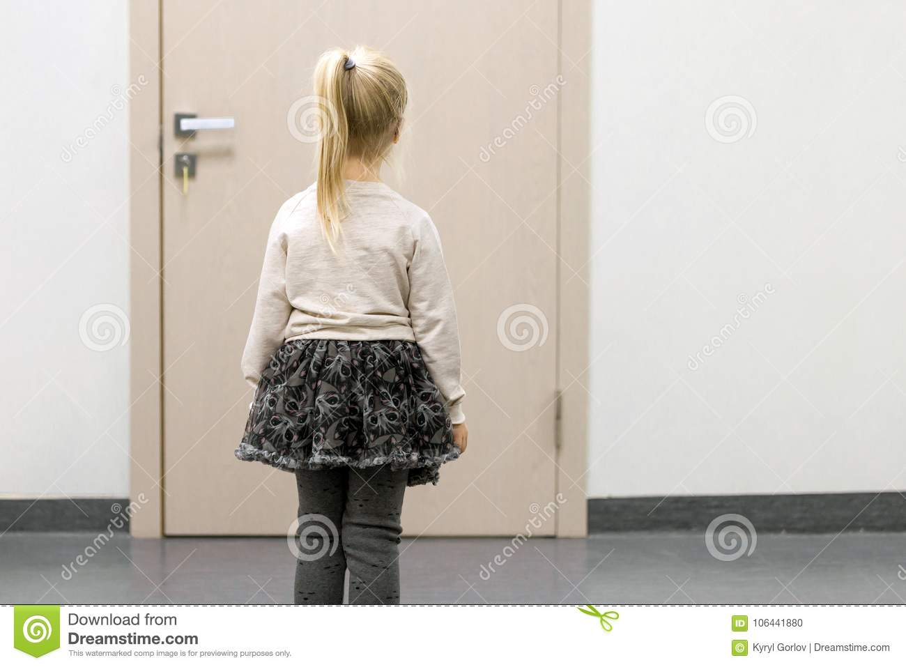 Little girl standing in front of doctors door