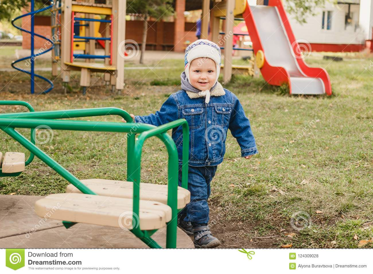 d652ff1b1 Little kid in jeans suit plays on the playground, happy boy spinning on the  carousel. More similar stock images