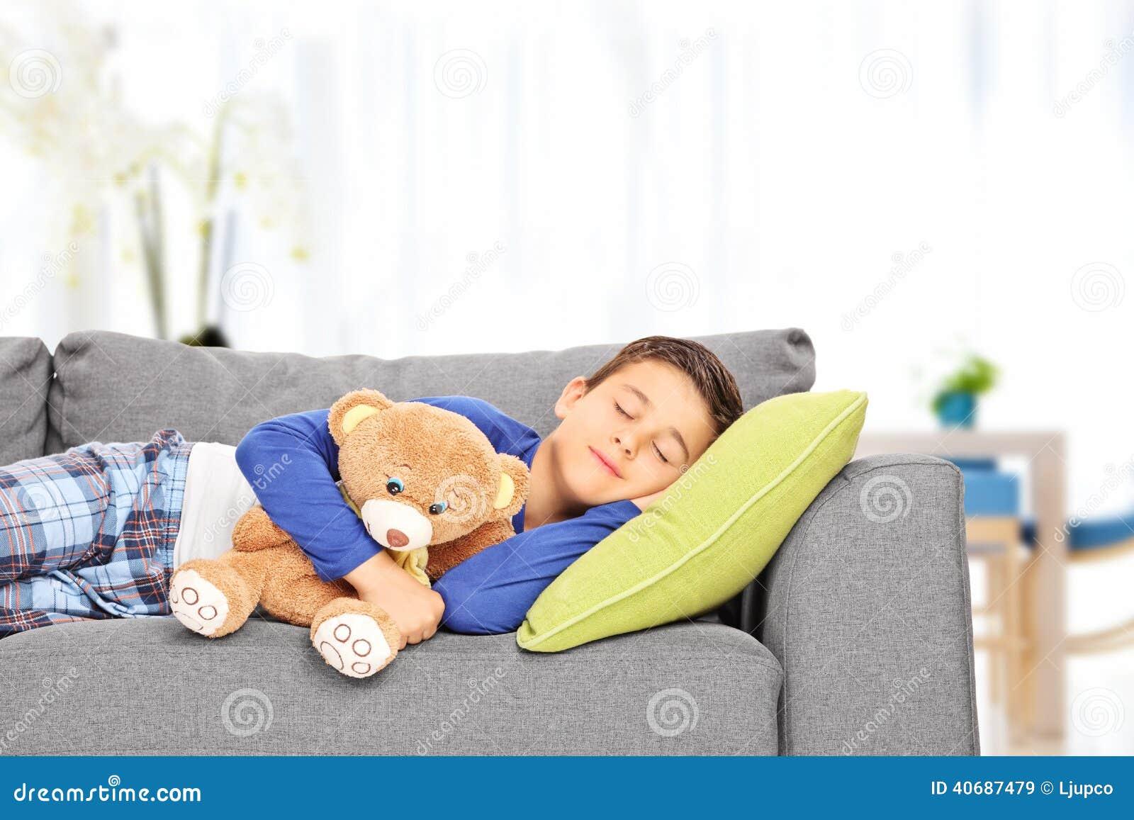 Little Kid Sleeping On Sofa With A Teddy Bear At Home Stock Photo ...