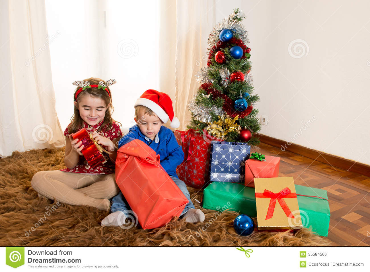 Little Kids On Rug Opening Christmas Presents Stock Photo - Image of ...