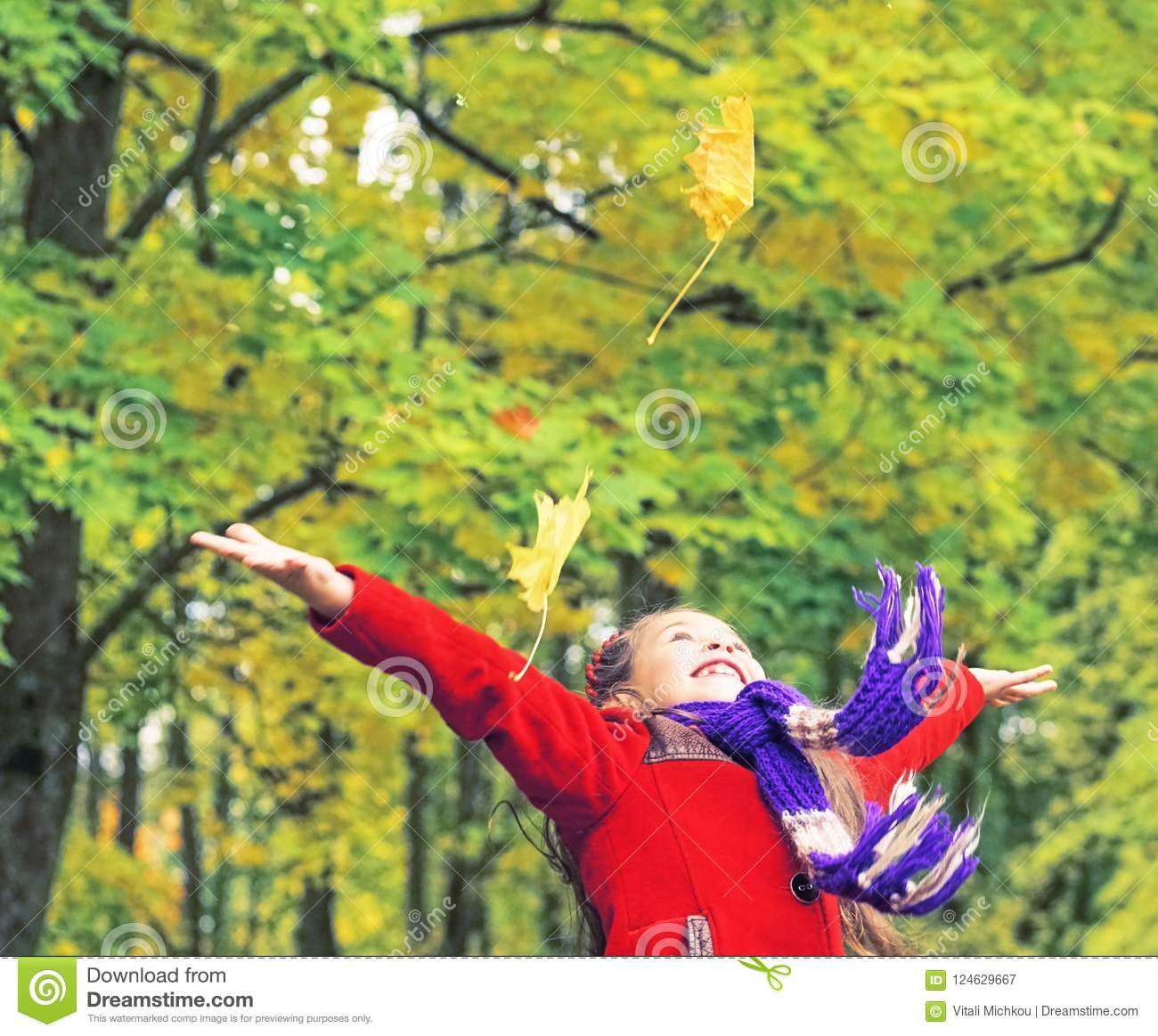 Little laughing pretty girl in red coat throws yellow leaves in autumn park