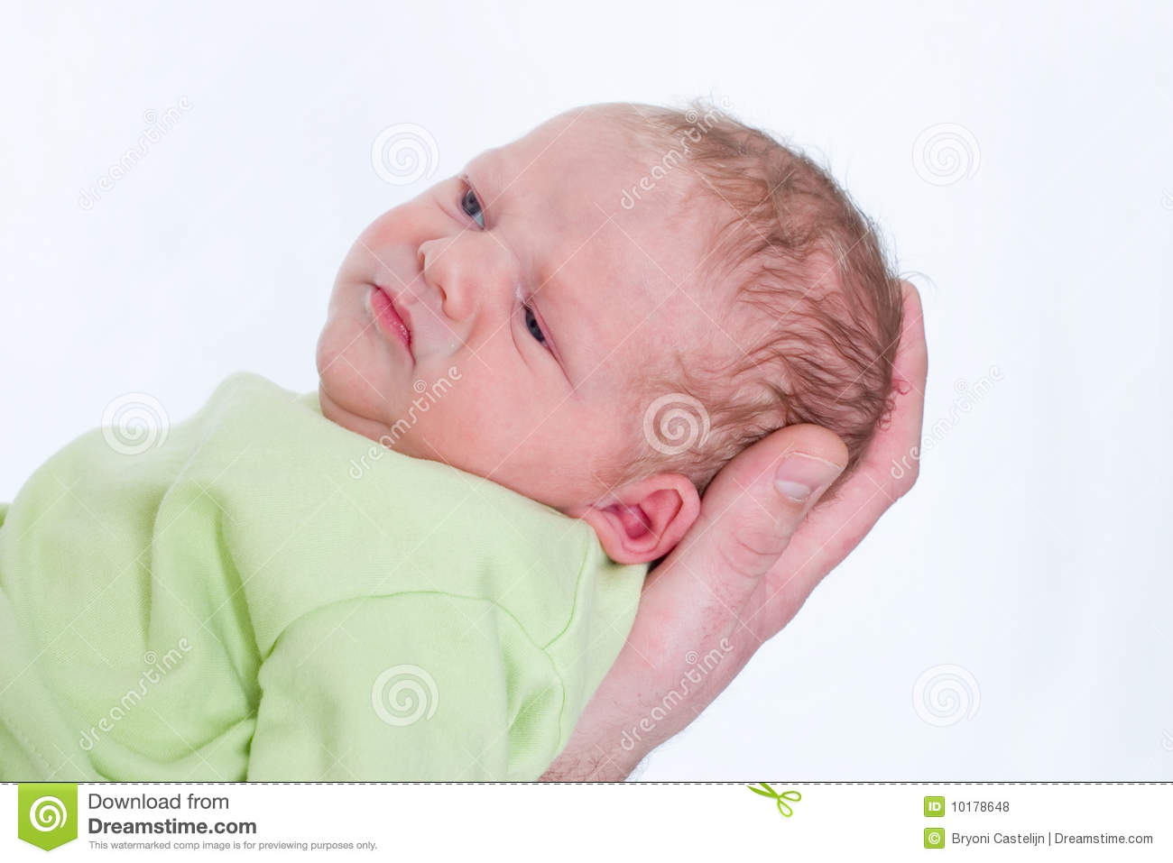 Little newborn baby on his fathers hand frowning