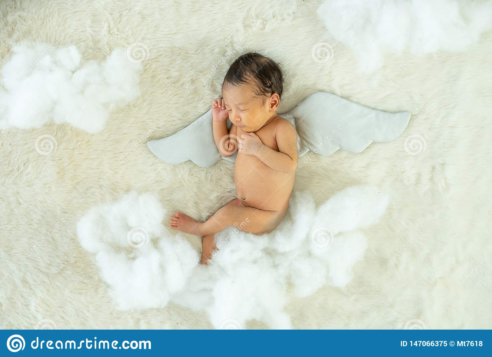 Little newborn baby is sleeping on white bed with wing accessory and fluffy pandas