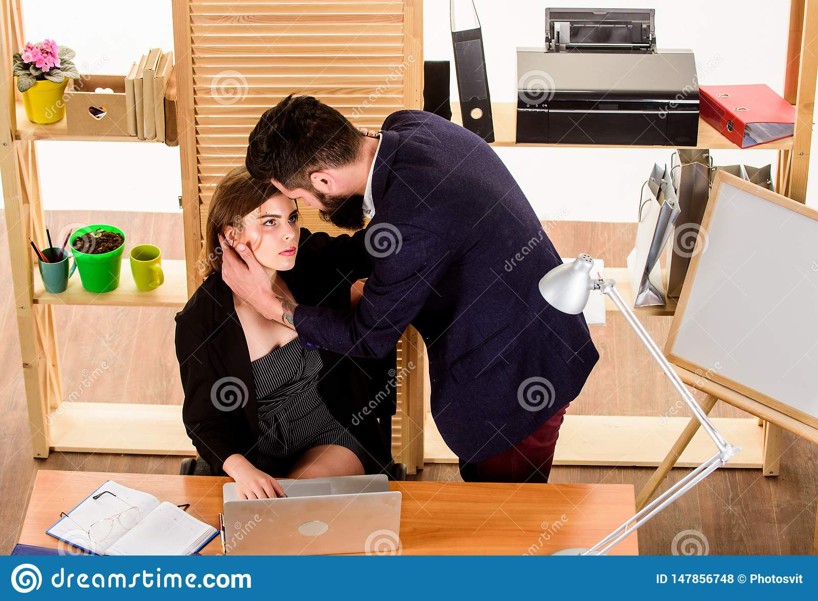 A little passion at work. Love affair of bearded man and sexy woman in office. Couple in love conducting affair at work