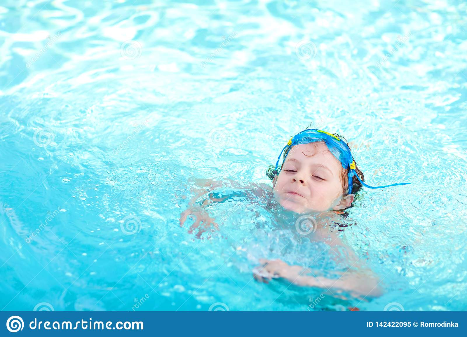 Little preschool kid boy making swim competition sport. Kid with swimming goggles reaching edge of the pool . Child