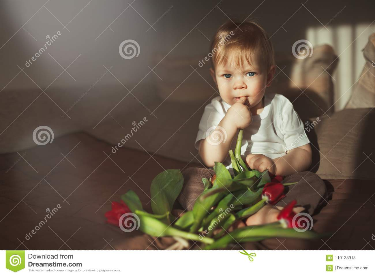 A little pretty boy looks into the camera and holds his finger in his mouth. Next to him is a bouquet of colorful tulips. Home and
