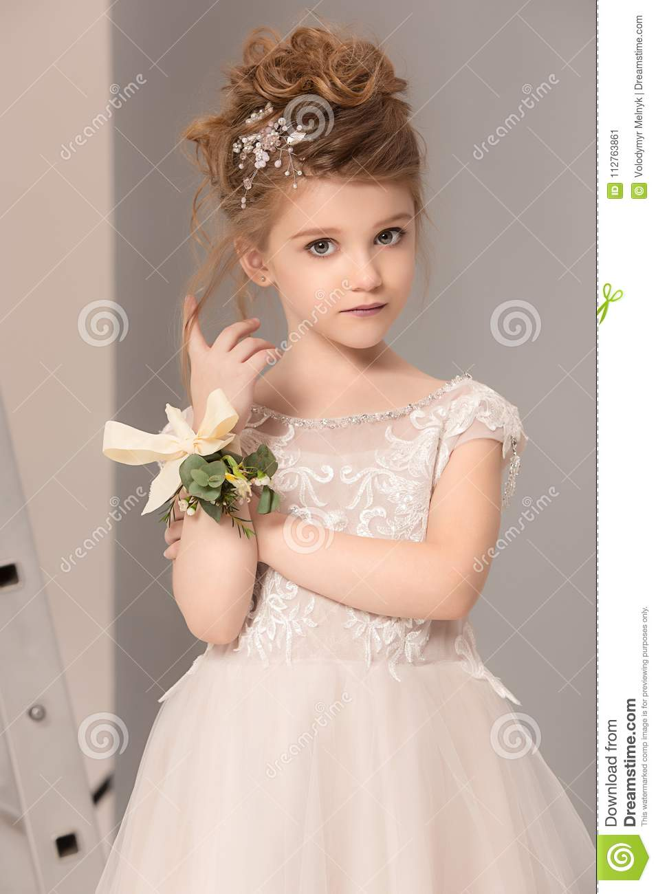 Little Pretty Girl With Flowers Dressed In Wedding Dresses Stock