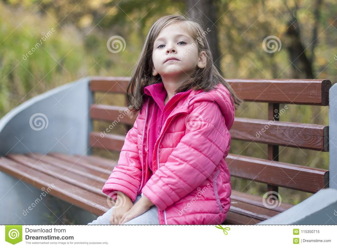 Little pretty girl in a pink coat sitting on a wood bench at the park in autumn. Emotional portrait