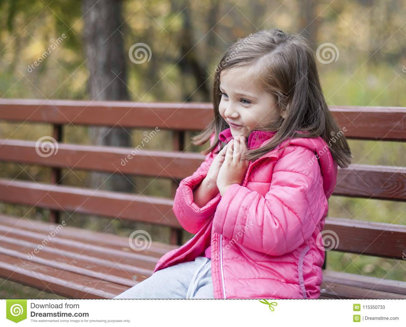 Little pretty girl in a pink coat sitting on a wood bench at the park in autumn. Emotional portrait. Childhood concept