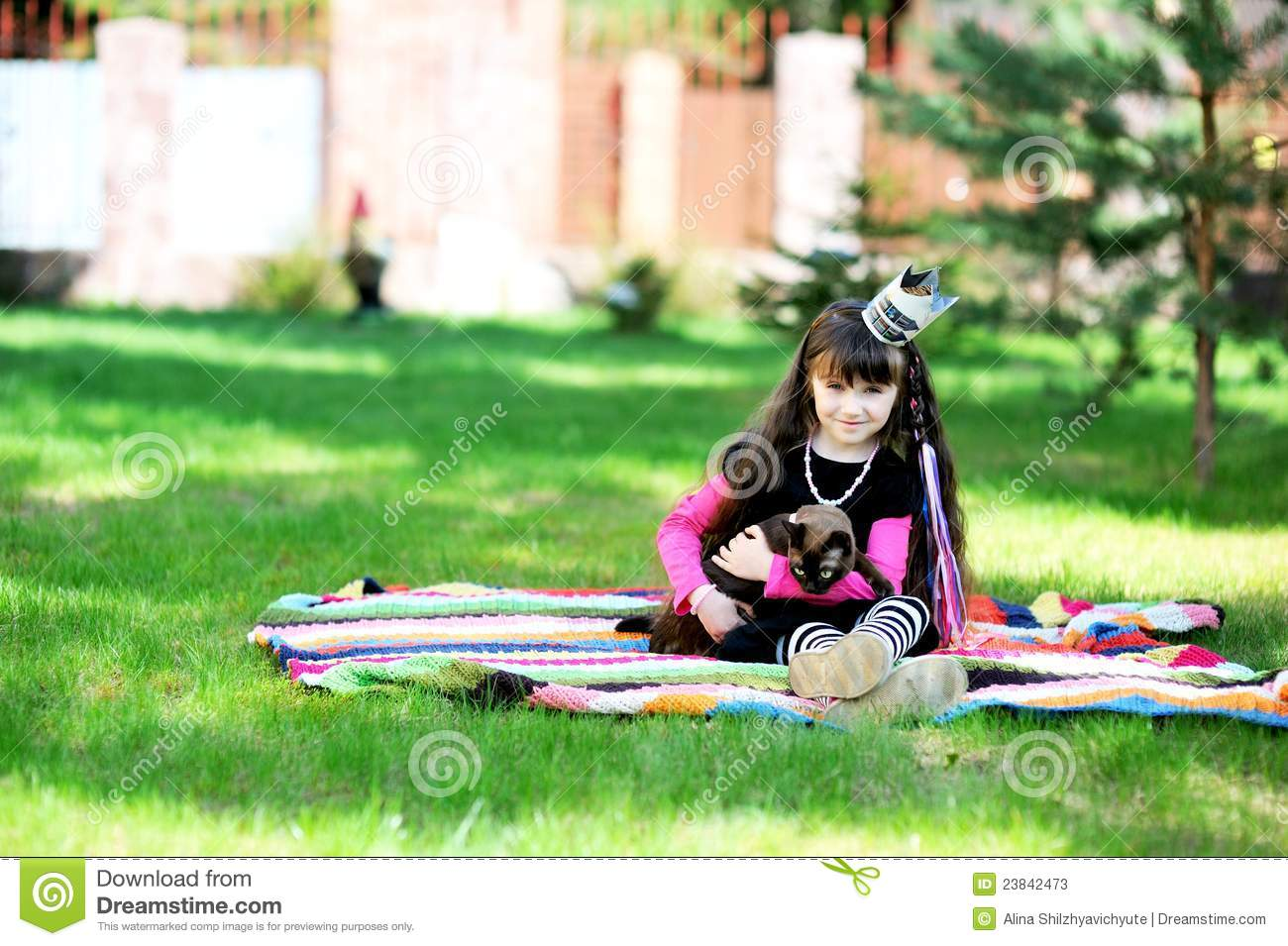 Little princess playing with burma cat outdoors