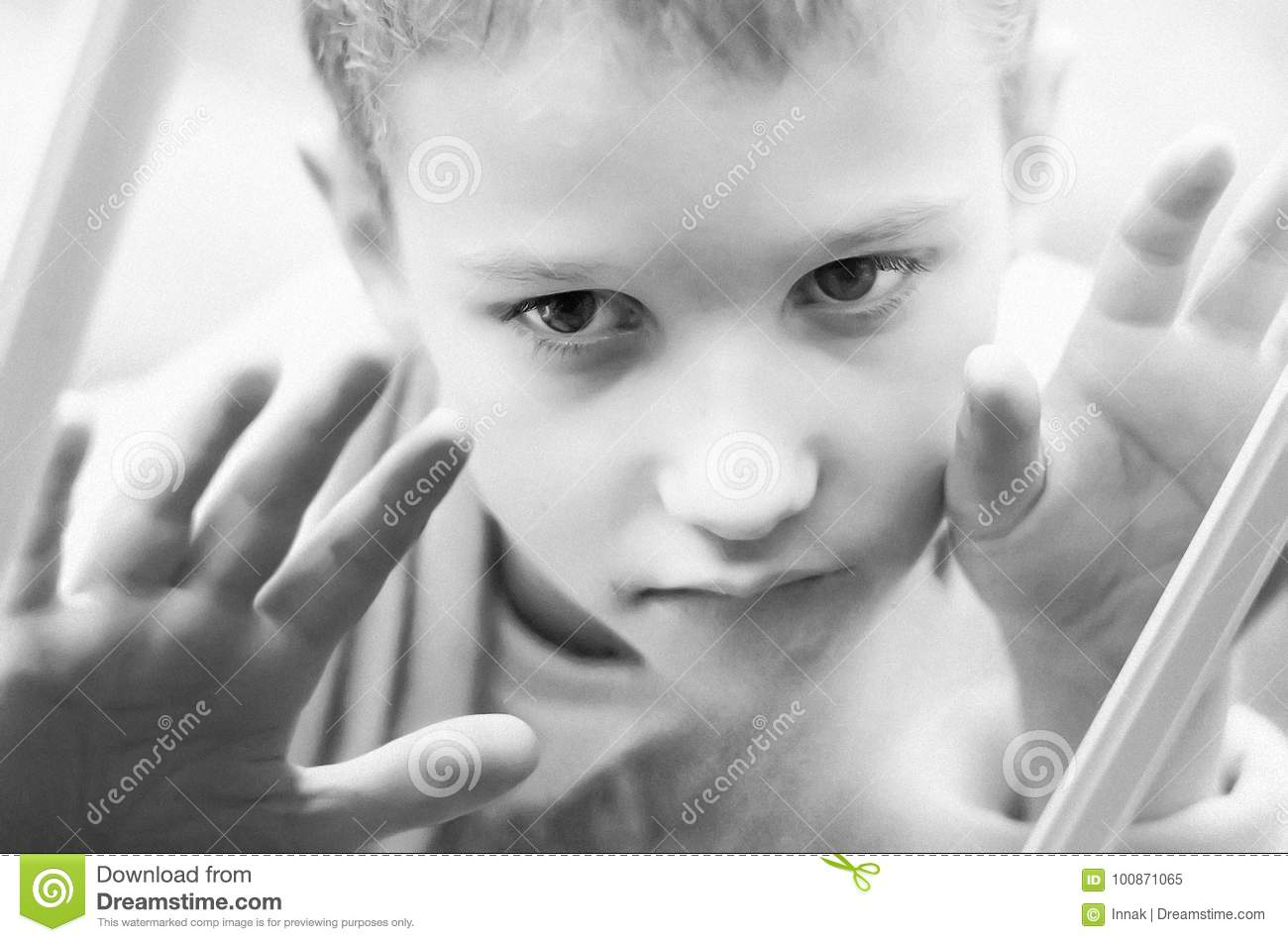 Little sad boy looks out the window. Black and white photo of a close-up child. Hungry child with big clear eyes eating bread