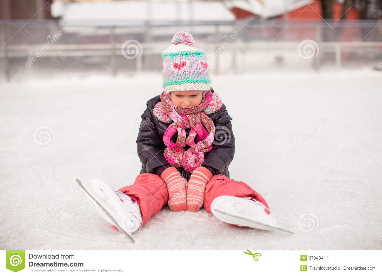 Little sad girl sitting on a skating rink after