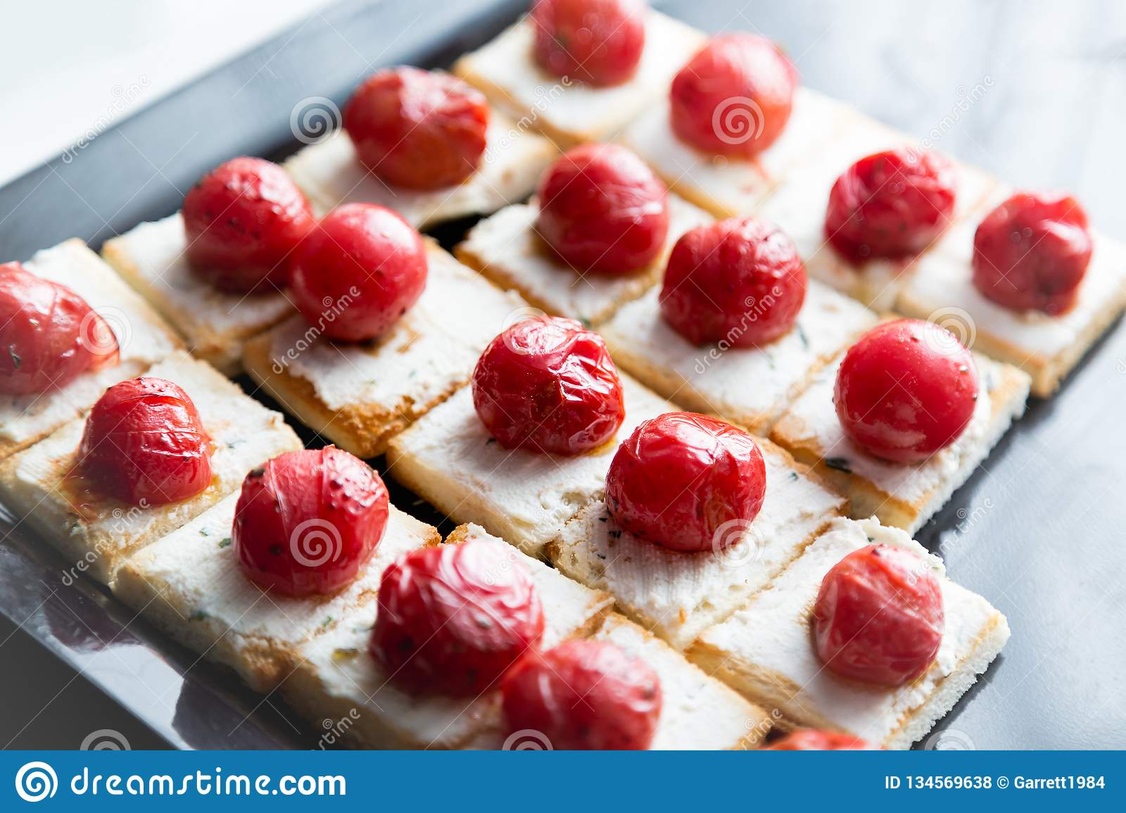 Little sandwiches with cheese and grilled cherry tomato. Catering food