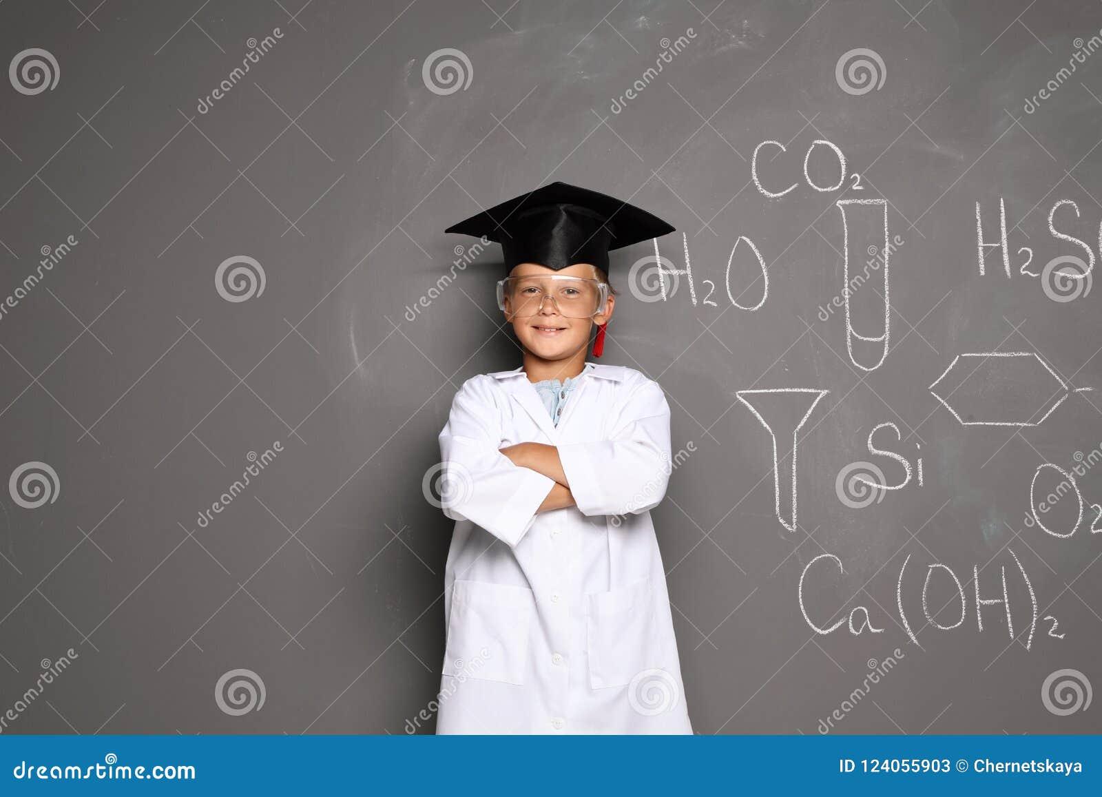 Little school child in laboratory uniform with graduate cap