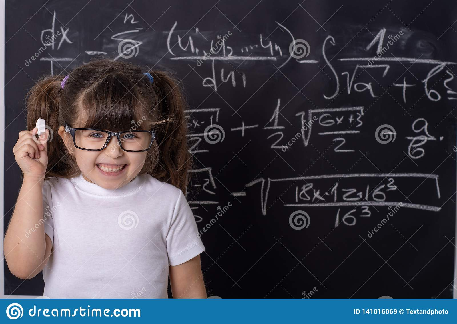 Little school girl in classroom. Clever kid