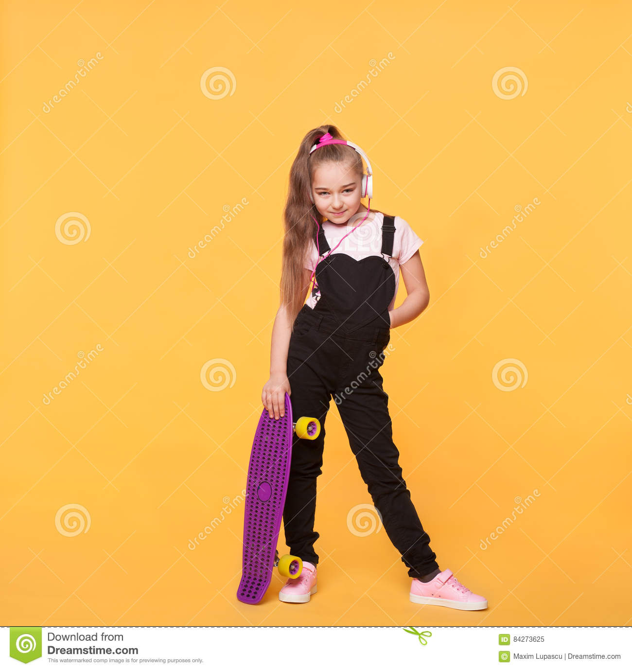 12a8a7a76162 Little school girl posing with skateboard and headphones. In the studio.  Full body size