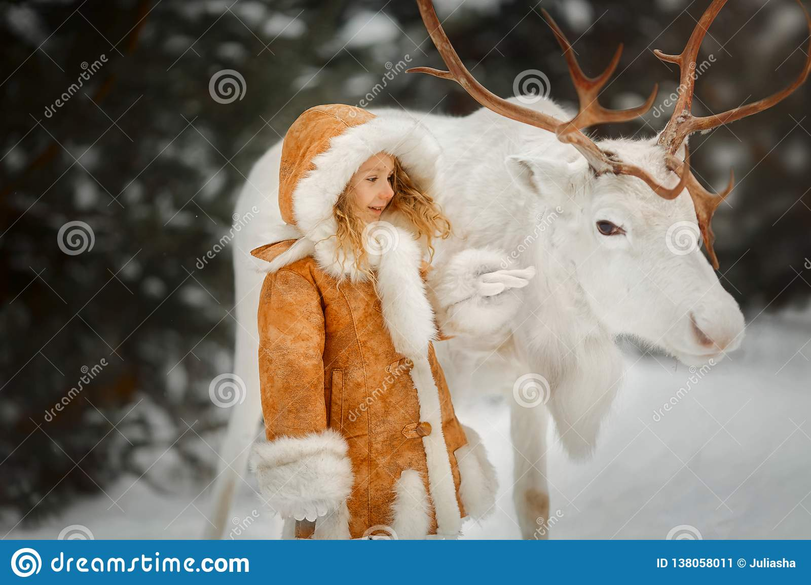 Portrait of beautiful Little girl in fur coat at winter forest