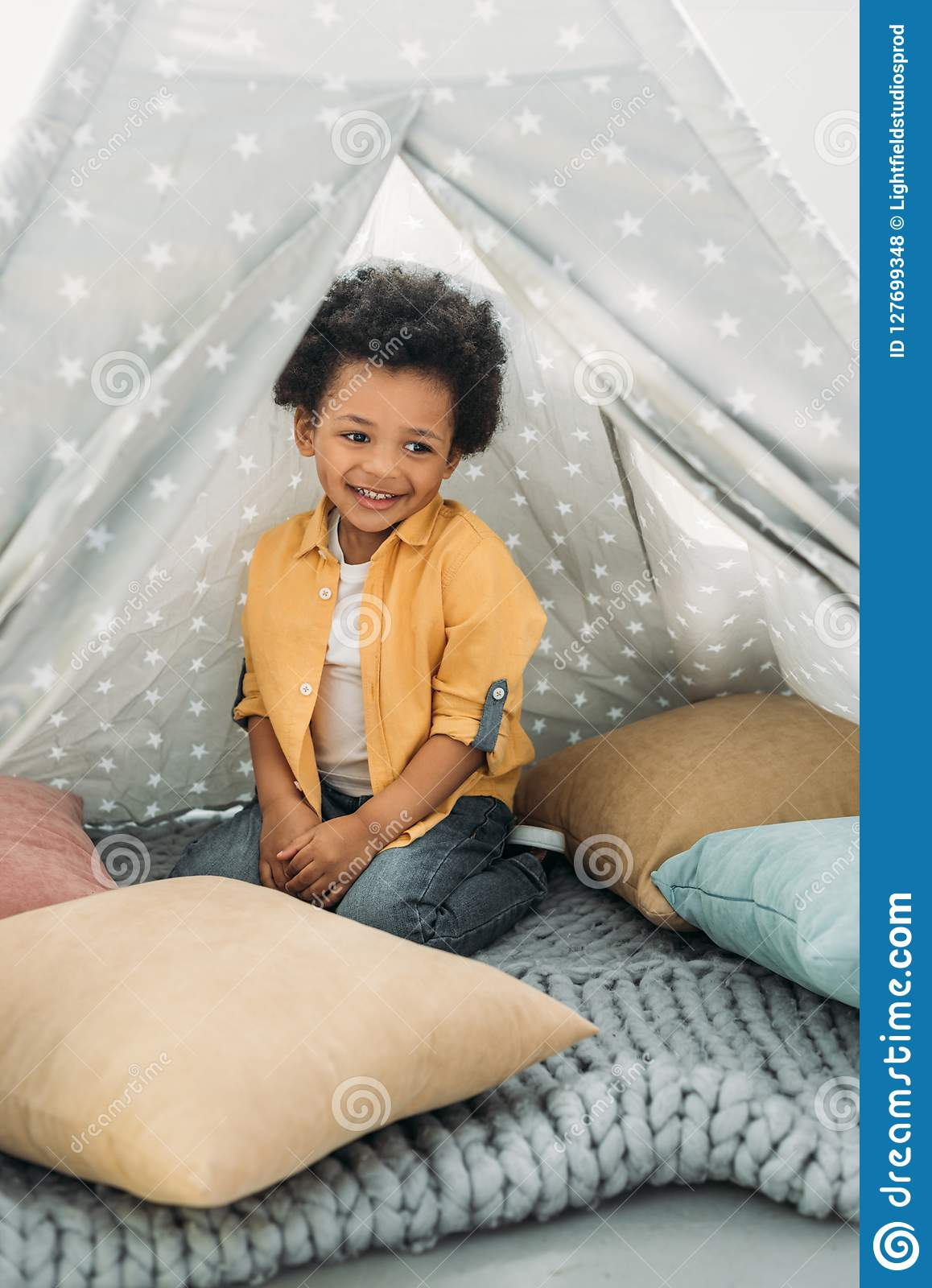little smiling african american boy sitting in teepee