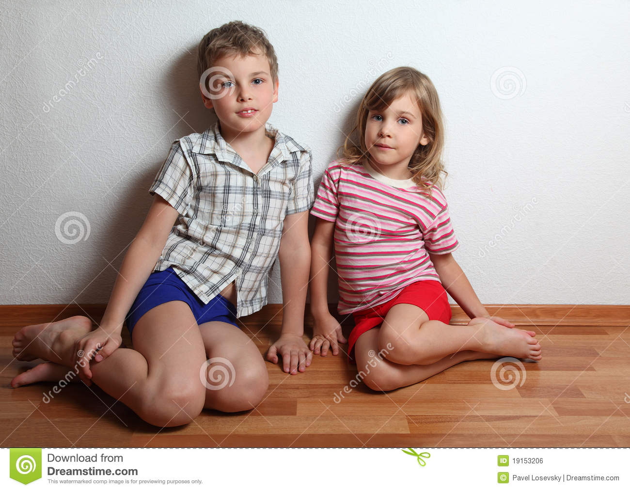 Little smiling boy and thoughtful girl sitting