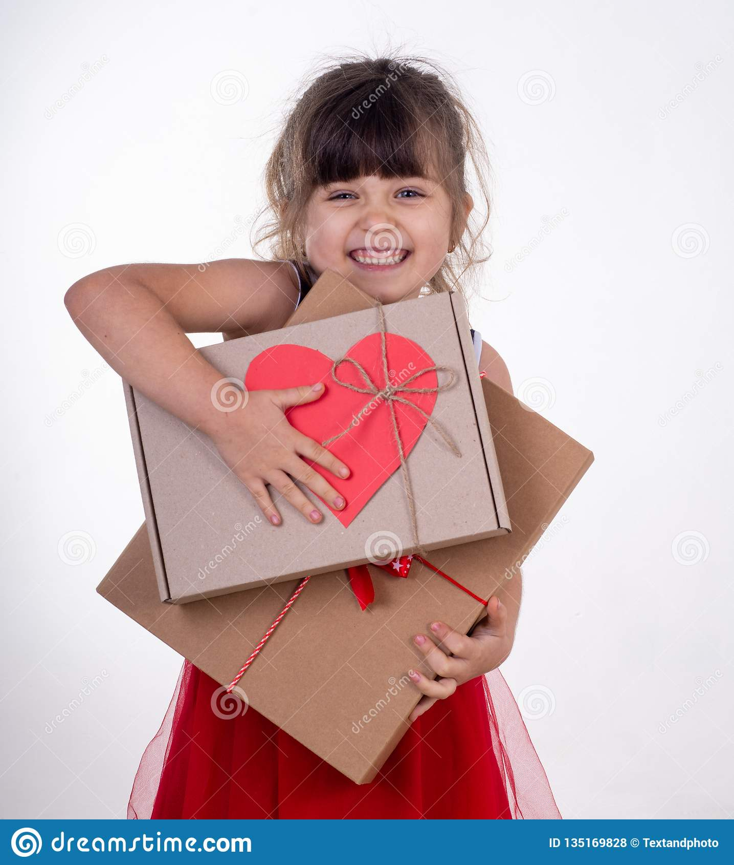 Little smiling girl holding present box isolated on white.