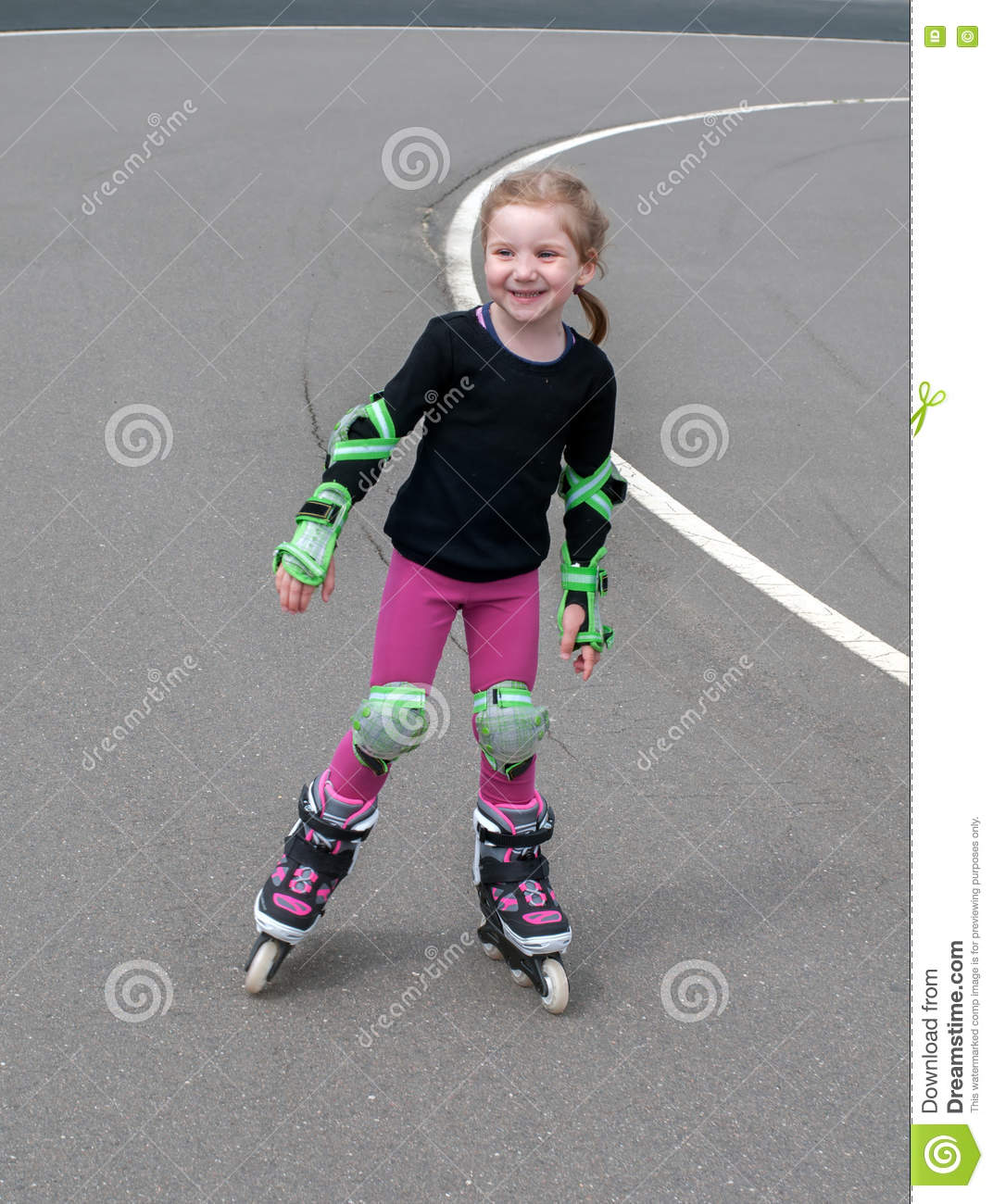 A little smiling girl practicing inline (roller) skating in the outdoor stadium