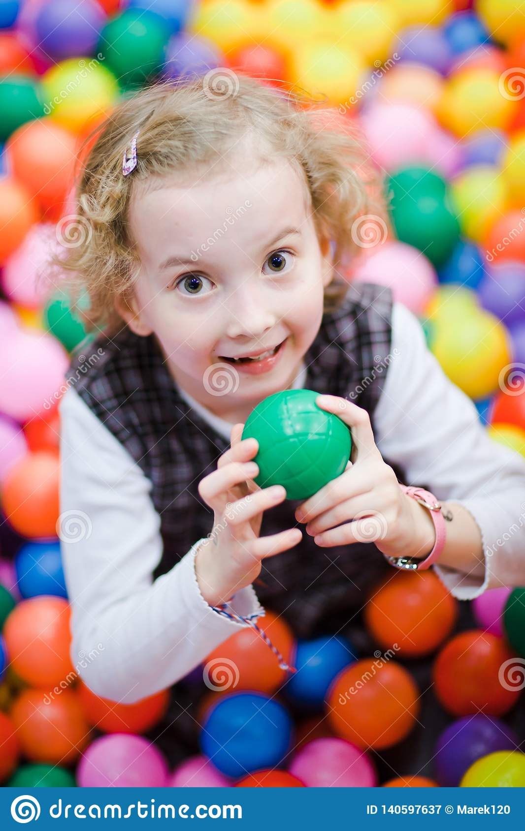 Little smiling girl sitting among a lot of colorful balls - Shallow focus on eyes