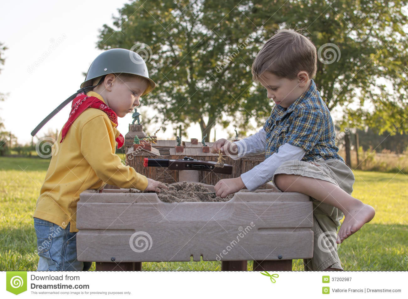Two little boys playing soldiers with green army men in a sandbox and