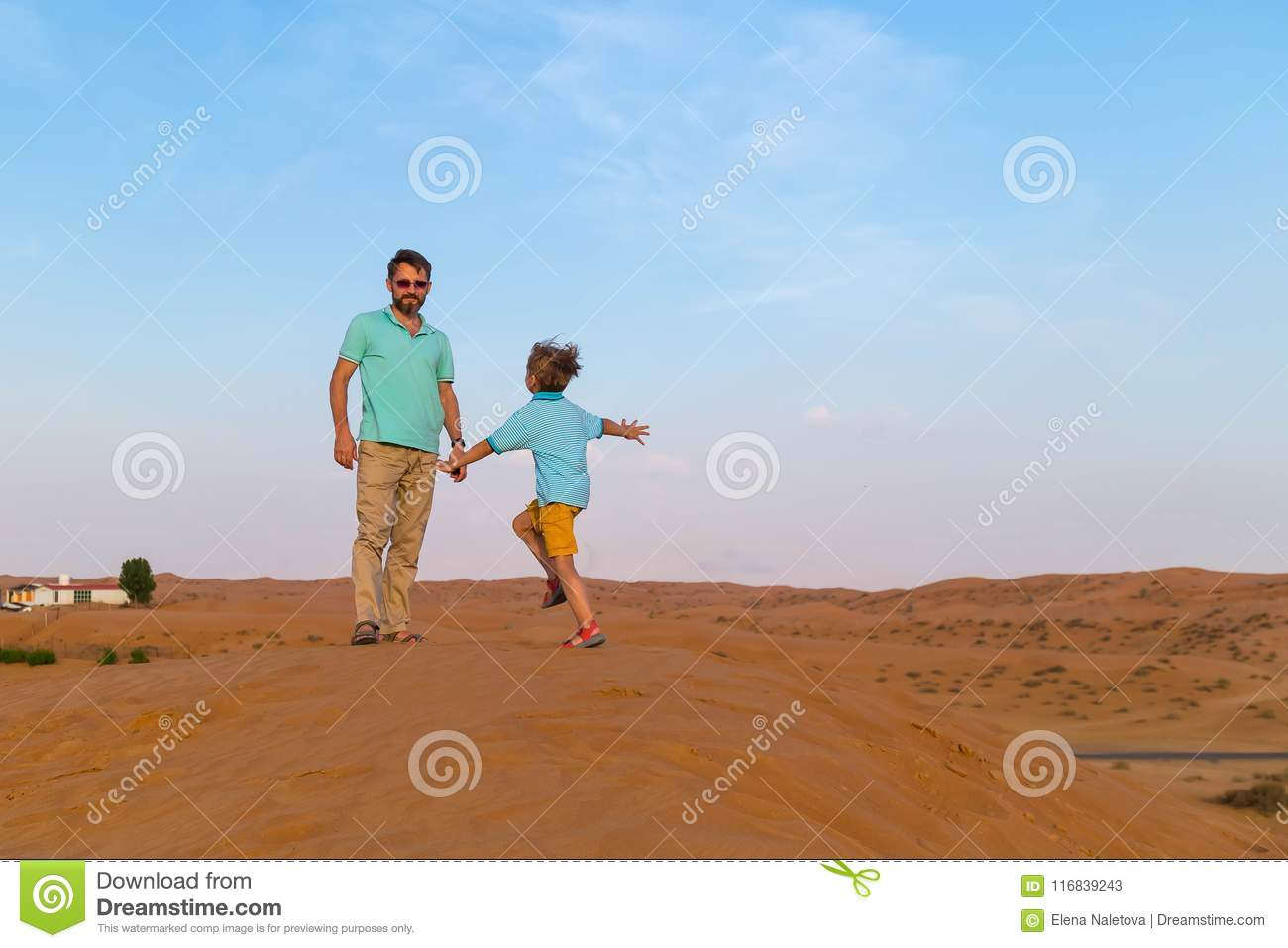 little son is runs on a meeting to the father on dunes in the hot desert