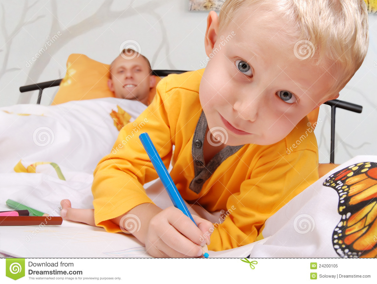 Little son drawing into the bed