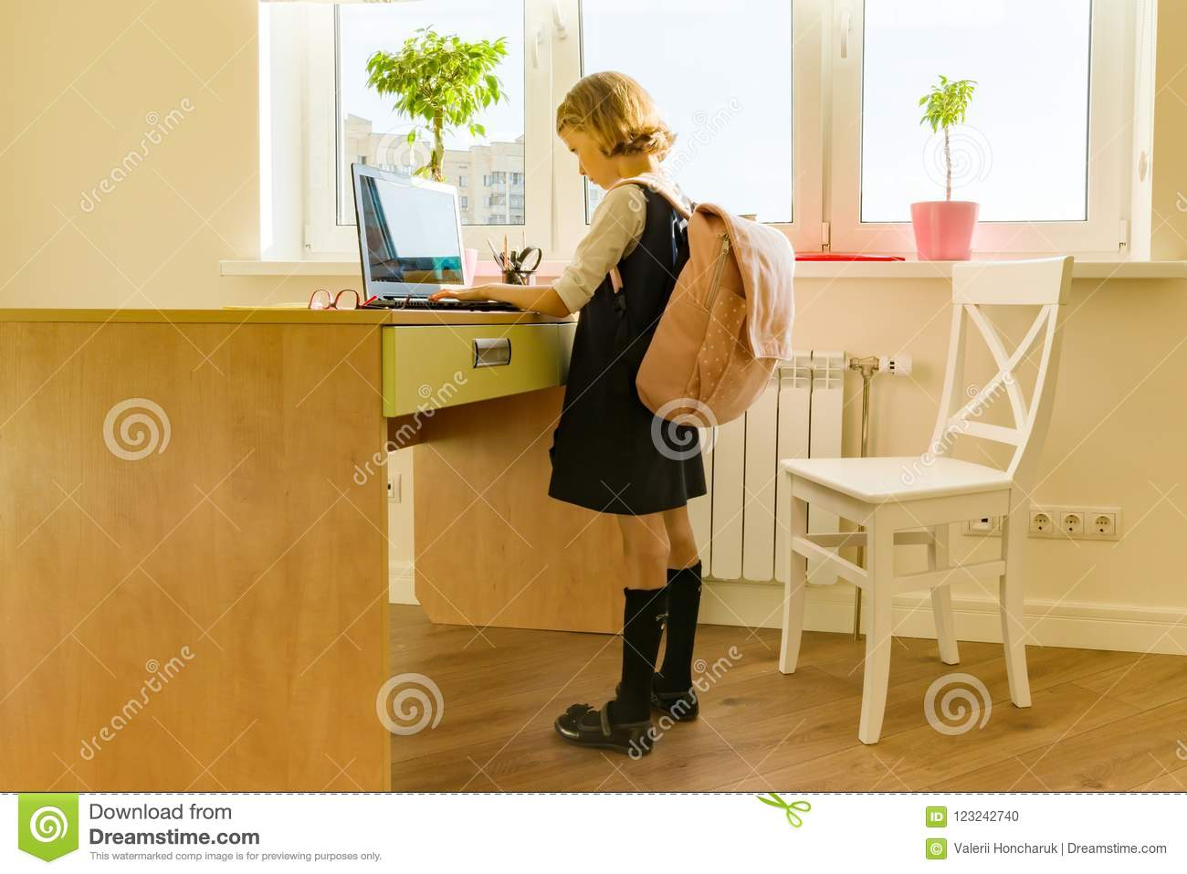 Little student girl of 8 years old in school uniform with a backpack uses laptop. School, education, knowledge and children.