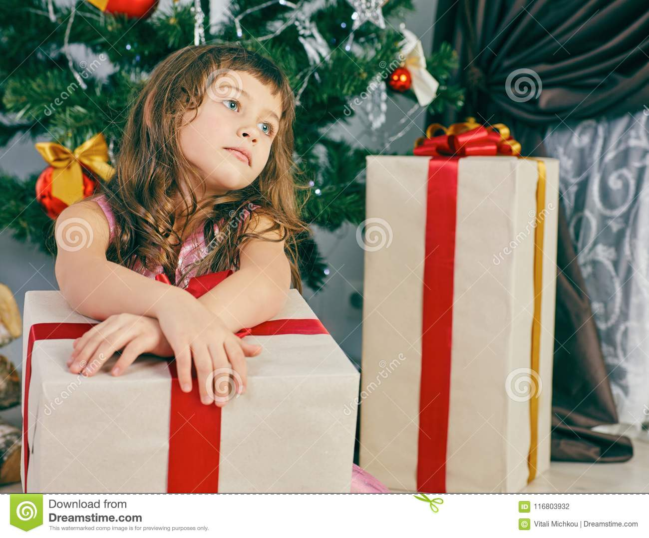 little thoughtful girl dreams near a christmas tree holding a big gift box