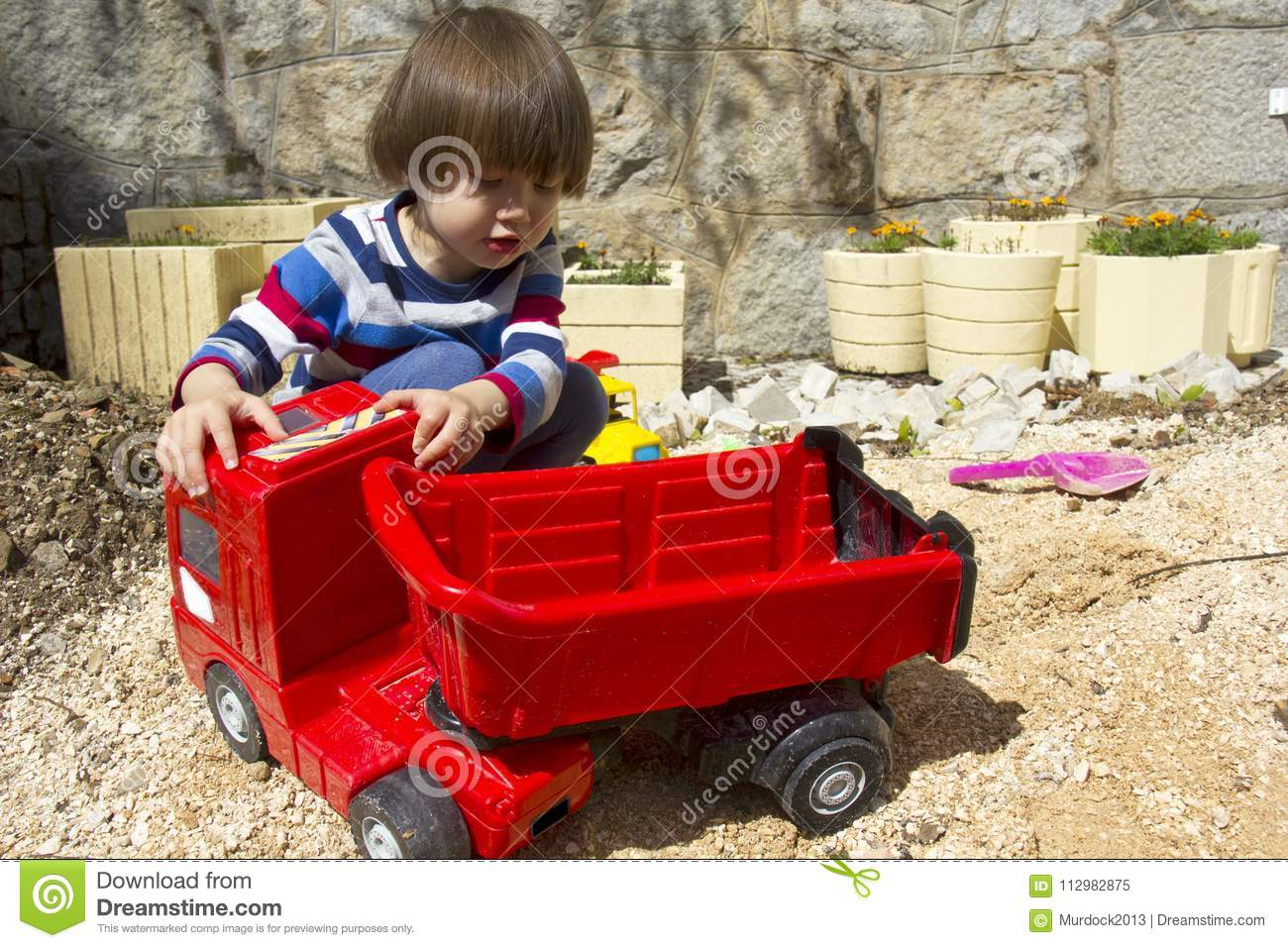 Little boy playing with toy digger and dumper truck.