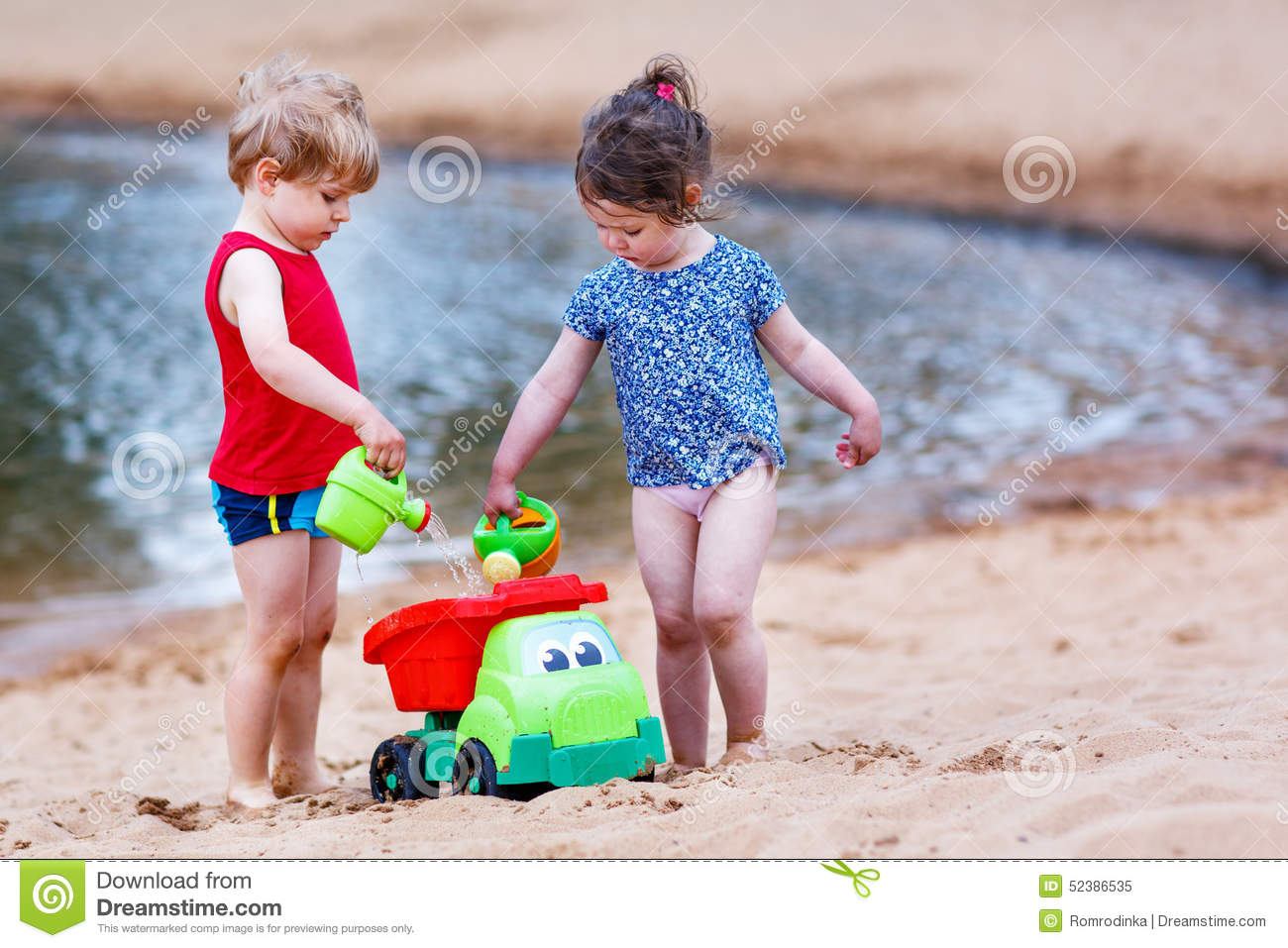 Lake Toys For Boys : Little toddler boy and girl playing together with sand