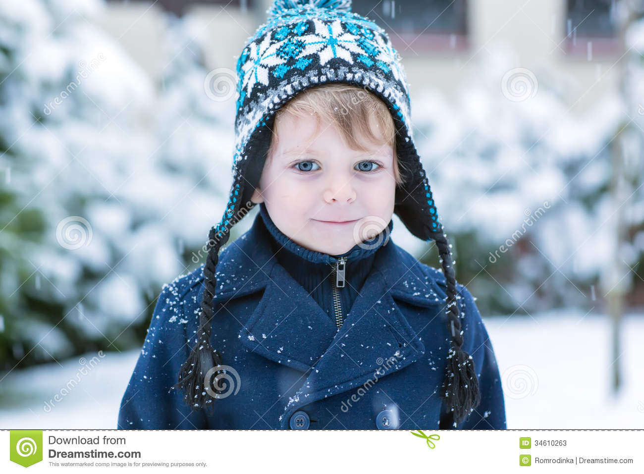 little toddler boy having fun with snow outdoors on