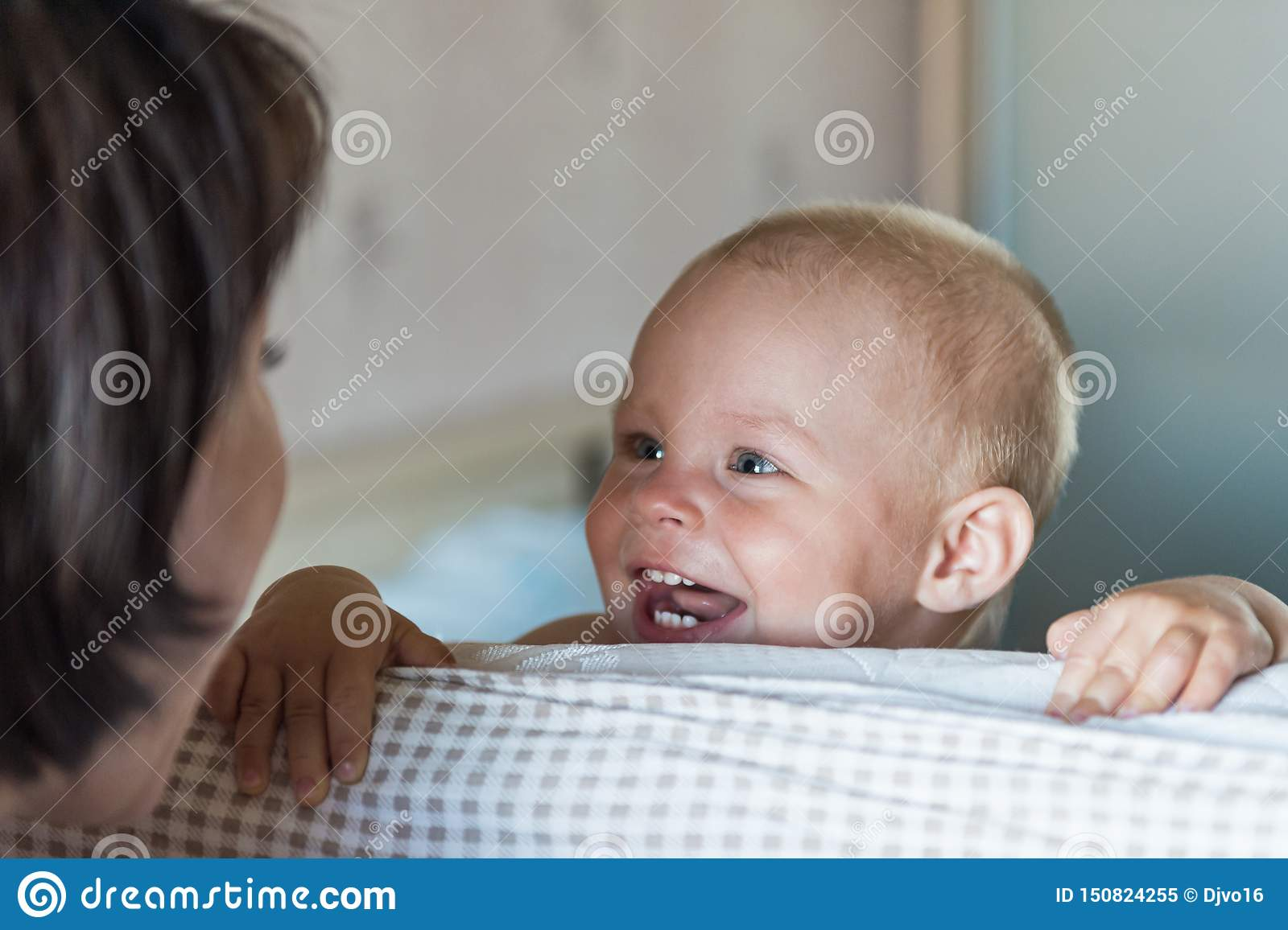 Little toddler boy playing on the bed. Cute kid smiling and hiding under cover. Palyful and mischievous eyes. Hide-and-seek.