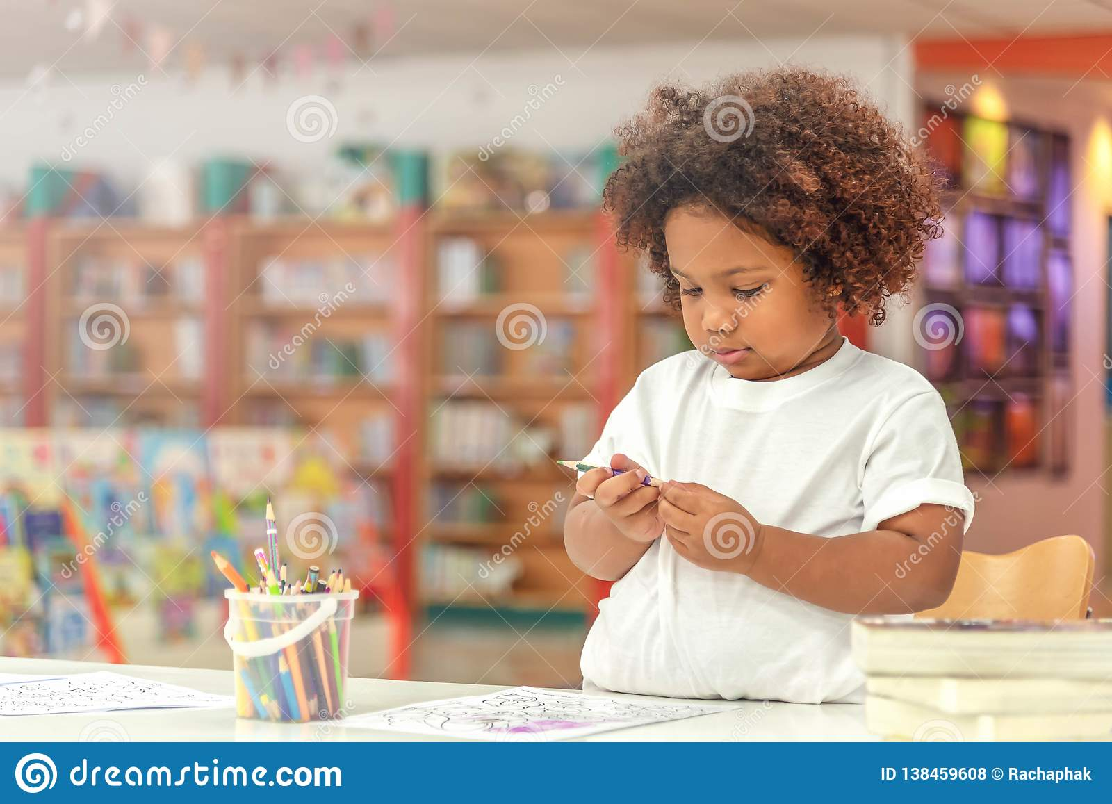 Little toddler girl concentrate on drawing. Mix African girl learn and play in the pre-school class. Children enjoy hand writing.