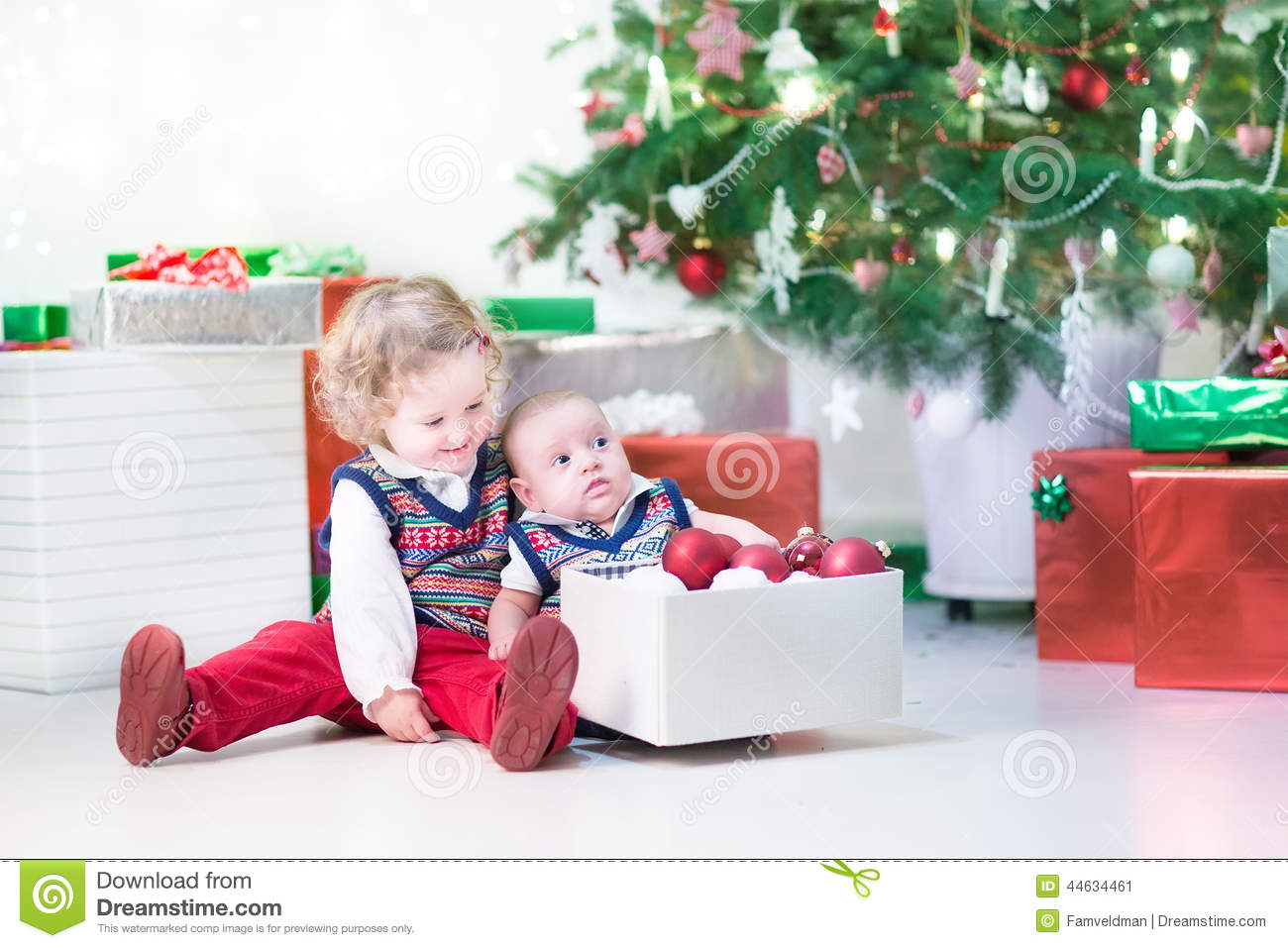 Little toddler girl and her newborn brother decorating Christmas tree