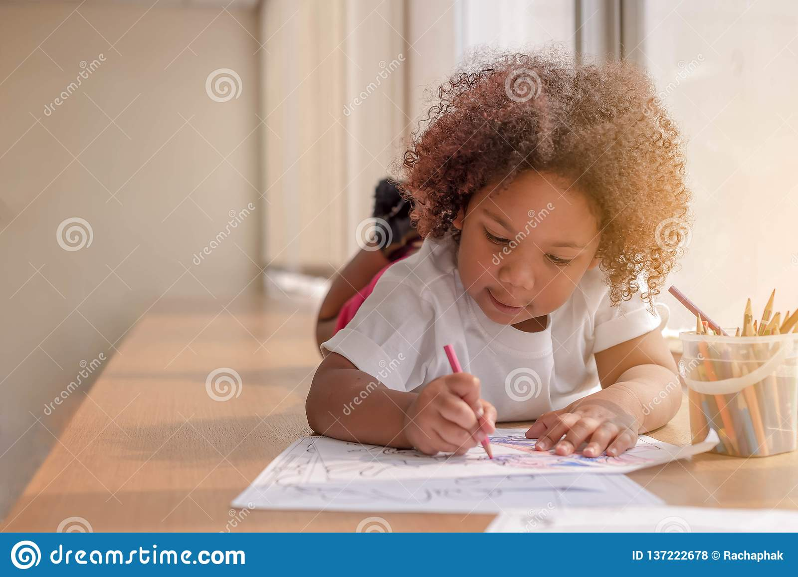 Little toddler girl laying down concentrate on drawing. Mix African girl learn and play in the pre-school class. Children enjoy
