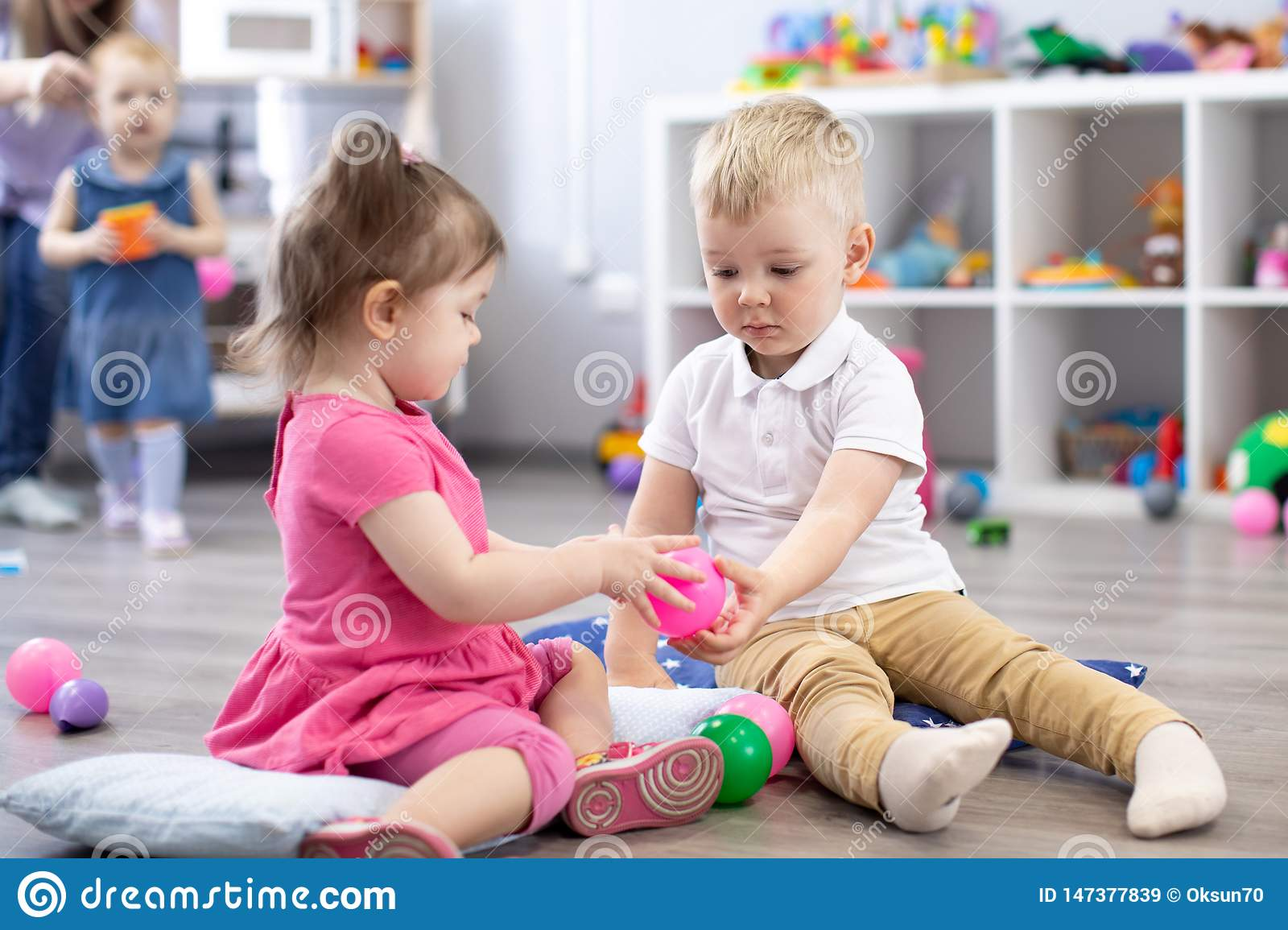 Little toddlers boy and a girl playing together in nursery room. Preschool children in day care centre