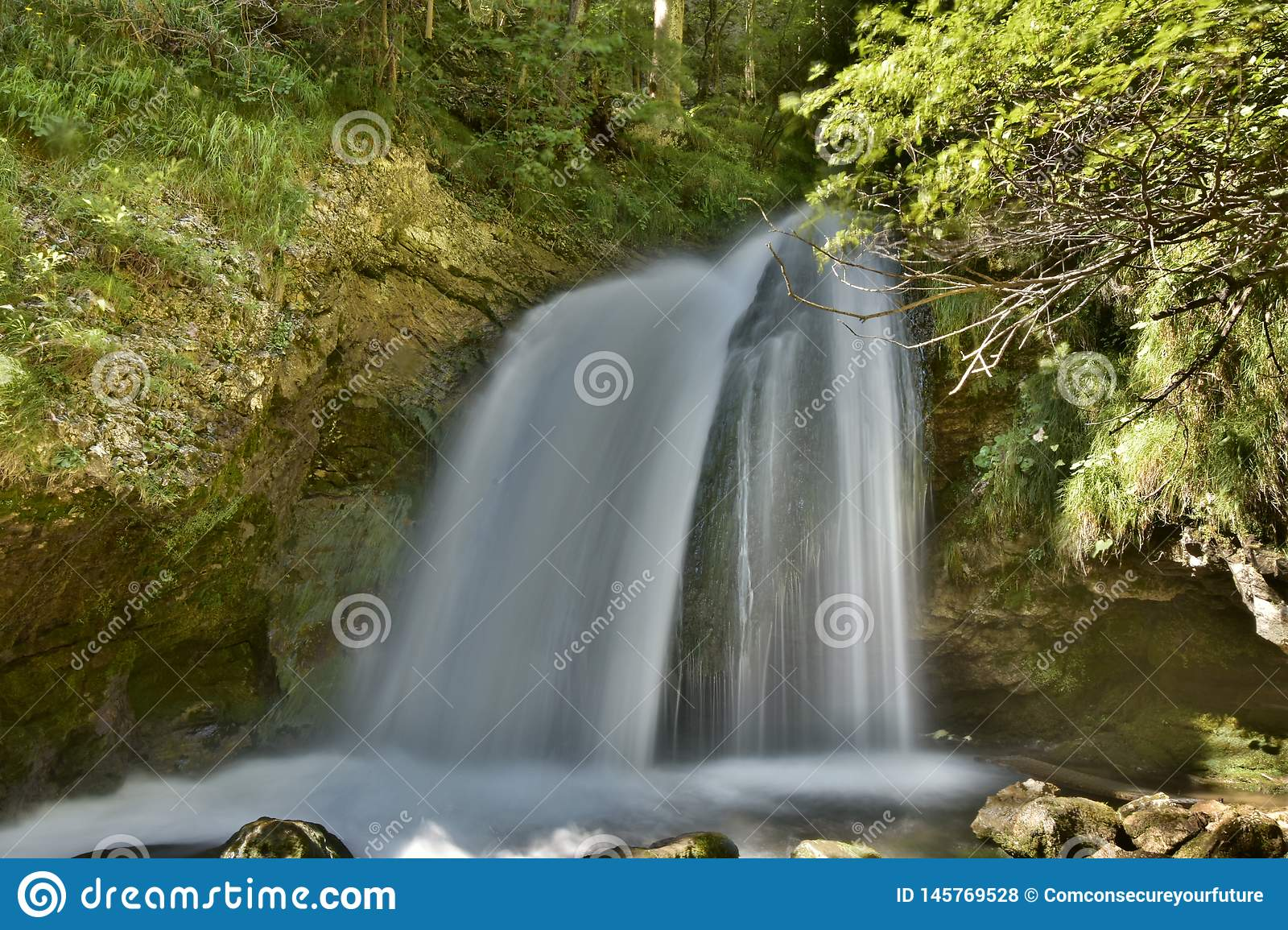Waterfall over a grotto in a shiny green forest