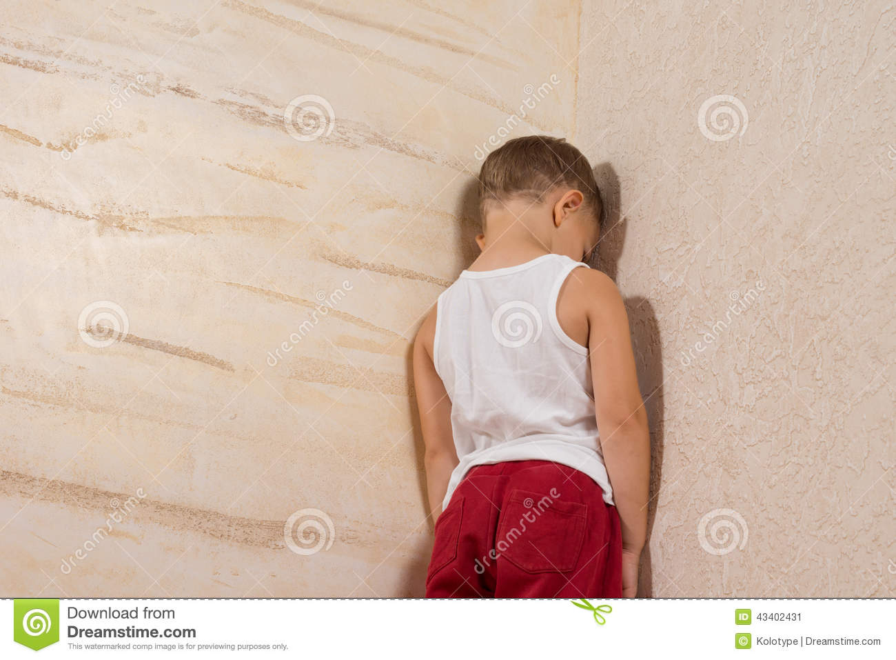 little young boy facing wooden wall stock photo image