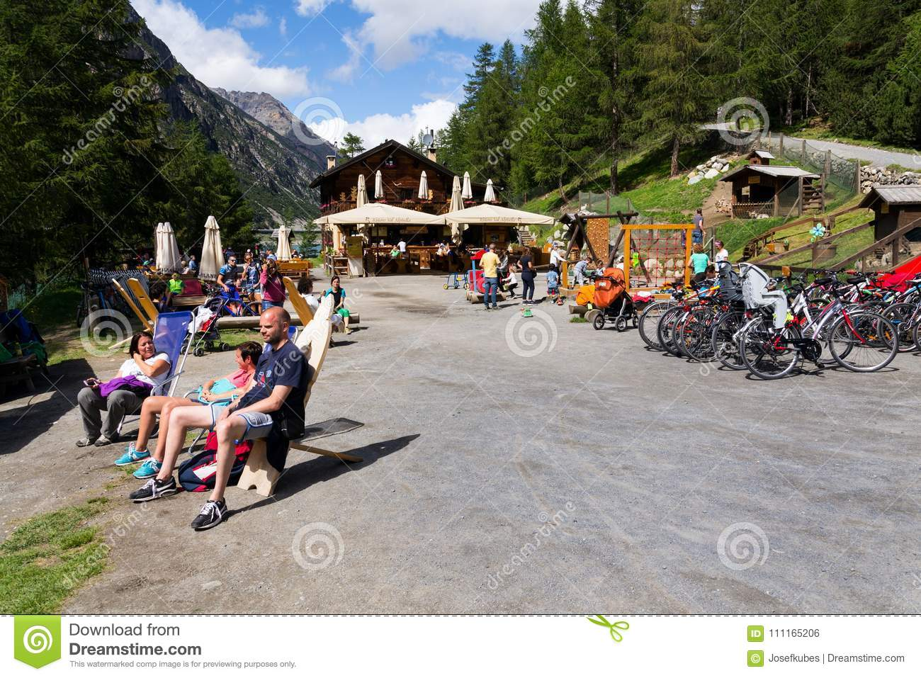 People sunbathing in front of restaurant with playing kids and bikes on bank of Lago di Livigno in Livigno, Italy