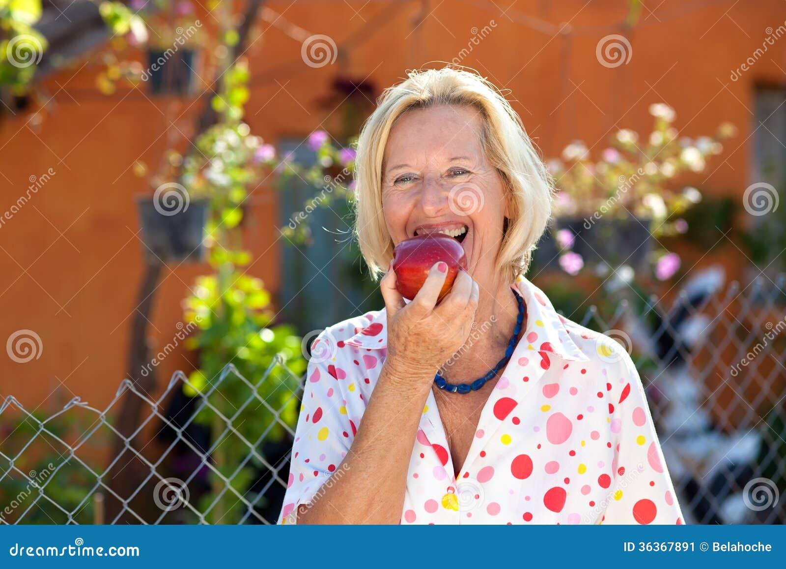 Livlig hög kvinna som tycker om ett rött äpple