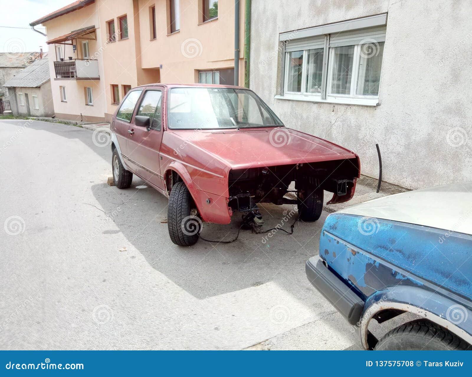 Livno/Bosnien och Hercegovina - Juni 28 2017: En sikt av en typisk gata i Livno Demonteraa bilar på vägrenen